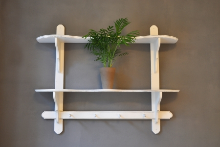 White shabby chick shelf on a gray wall with a green plant