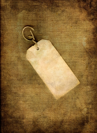 Blank vintage, paper tag on linen in grunge.