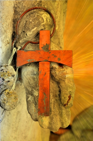An old rusty cross in a holy hand with glowing rays. Stock Photo - 16137120