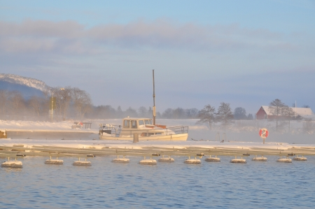 Sunset over foggy harbor in winter with sailboat. photo