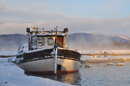 Boat docked in misty wintertime. photo