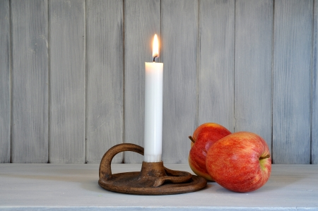 Candle in a handmade candle stick and two red apples in a sparse composition