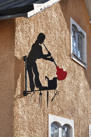 A glass blower as a sign on a building wall.