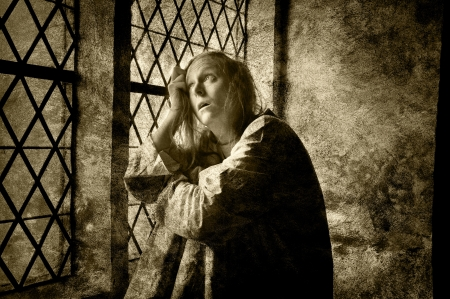 Mentally ill woman looking out of a window in a medieval building,