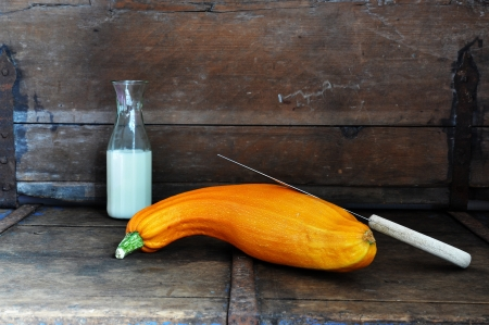 rustic kitchen: Yellow squash with knife and milk in a rustic kitchen Stock Photo