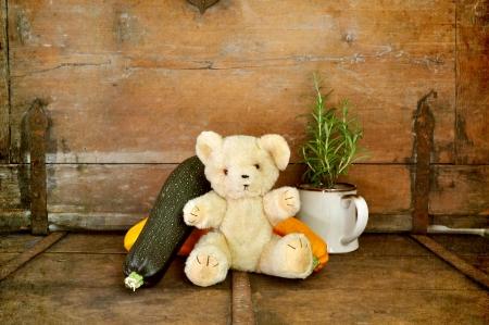 Old teddy bear enjoys vegetables, photo