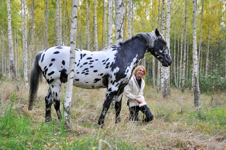 Woman and white horse with black spots in a birch forest