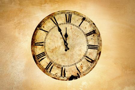 Reloj de la vendimia en la pared rugosa.