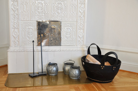 Old fashioned tiled stove with wood in a basket in the living room
