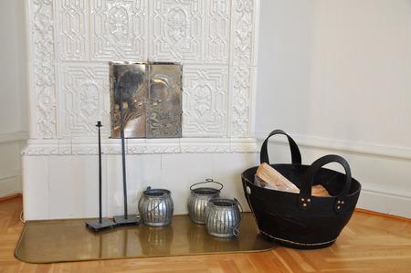 Ouderwetse tegelkachel met hout in een mand in de woonkamer