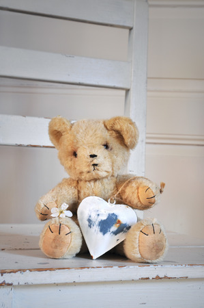 Vintage teddy bear from the 1960s with heart in shabby chic  photo