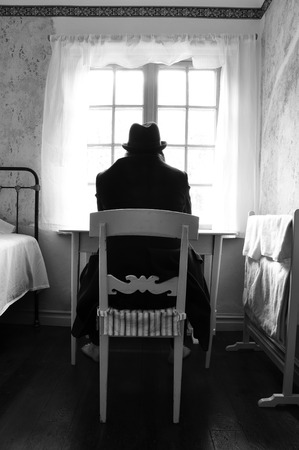 Male mental patient sitting in front of a window with hat and black coat, barefoot