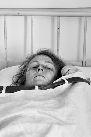 Woman with doll tied up in bed in a psychiatric ward. photo