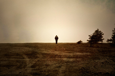solitude: Image textured with soft sandstone of human walking alone on a moor.