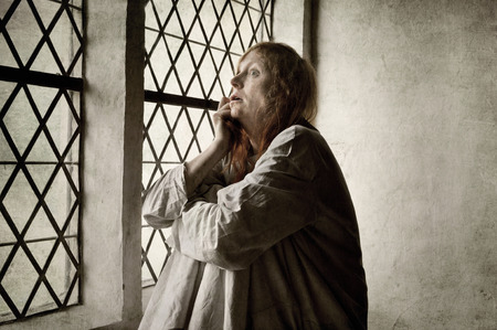 Crazy woman by the window of a medieval asylum