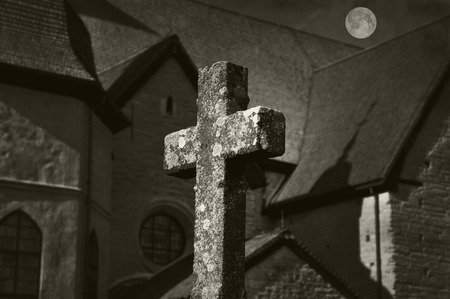 christian halloween: Cross in front of a church with full moon in black and white. Stock Photo