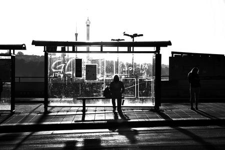 Straatfotografie van iemand wating bij een bushalte in zwart-wit.