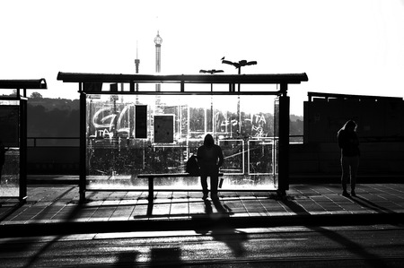 people on street: Street photography of someone wating at a busstop in black and white.