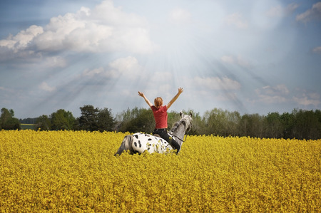 adult rape: Woman on horse with arms streched towards sun ray. Stock Photo