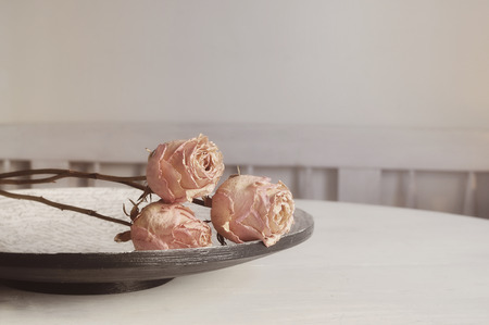 rose flower: Sparse image of soft pink roses on a wooden plate in french style.