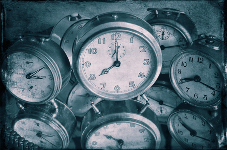 Closeup of textured image of vintage alarm clocks in blue.