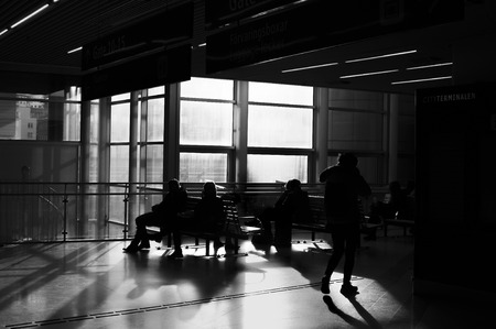 unrecognisable people: Unrecognisable, backlit people waiting in a terminal for bus or train. Black and white image.