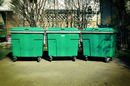 Three green plastic garbage cans in a backyard.