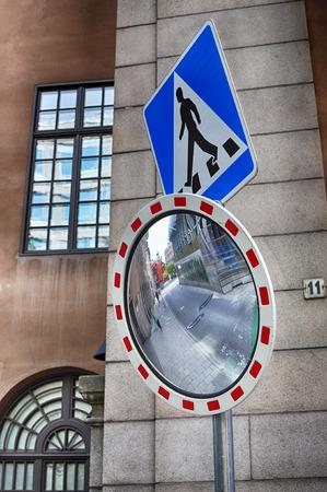 reflexion: espejo de esquina en el cruce con irreconocibles personas caminando la calle en la reflexión. Foto de archivo