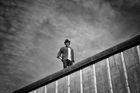 man looking down: Young man looking down from roof, dramatic skies.