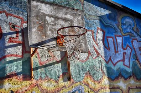 Basketball hoop on urban wall.