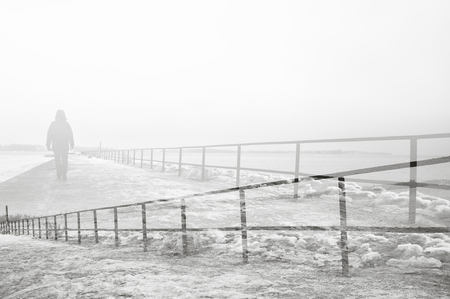 Black and white double exposure of person walking on foggy pier.