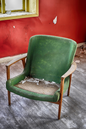 Old green chair inside abandoned house with red walls.