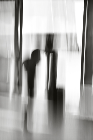 Motion blur of two shadows of two people talking in doorway.