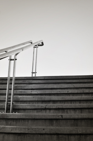 Cement steps with handrail in metal. Sparse composition against sky.