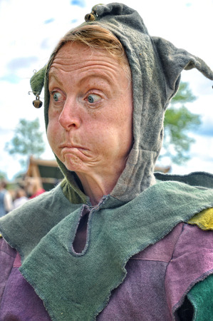 Woman dressed as jester with funny face.