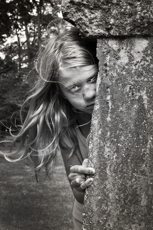 headstone: Scary child next to a headstone in black and white.