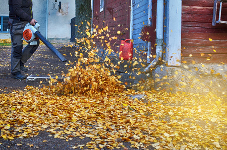 blower: Female worker with leaf blower in the fall.