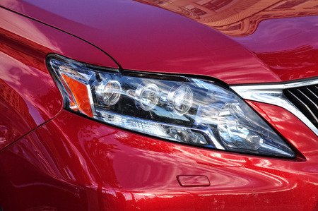 reflexion: Primer plano de los faros de un automóvil deportivo de color rojo con la reflexión urbana.