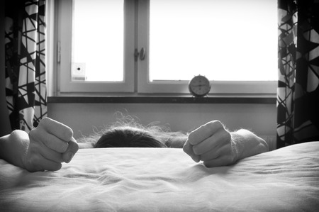 violated: Violated woman by the bed with clenched fists.