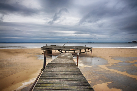 Old jetty on the beack a dramatic winter day. Stock Photo
