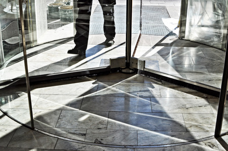 Feet walking in revolving door.