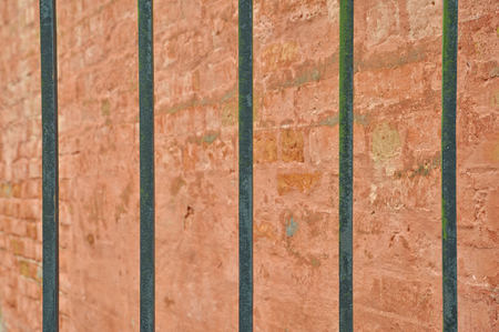 Closeup of old iron bars with ancient brick wall in the background. Stock Photo