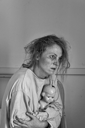 Mental patient holding a doll, black and white image. Stock Photo