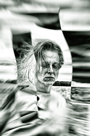 Motion blur abstract portrait of woman with closed eyes, monochromatic.