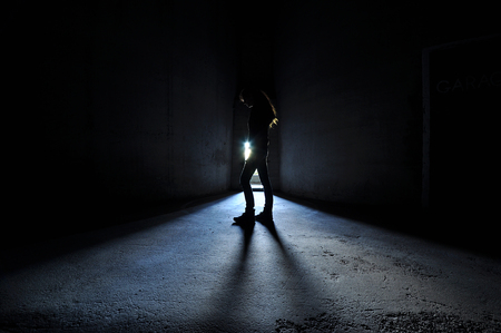 Backlit woman standing in doorway thinking, blue light.