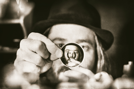 Mad scientist looking through a optic lens, grainy textured sepia image.
