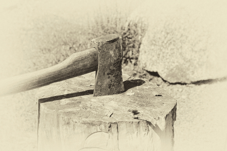 Slightly textured image in sepia of axe in wooden block.