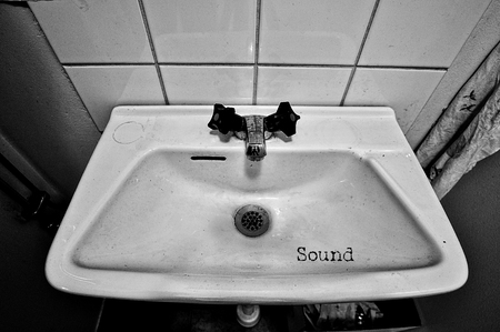 Closeup of a grungy sink in black and white with the word sound. Stock Photo