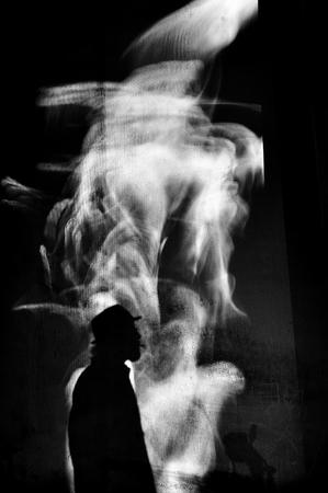Smoky black and white image of silhouette of man smoking cigar.