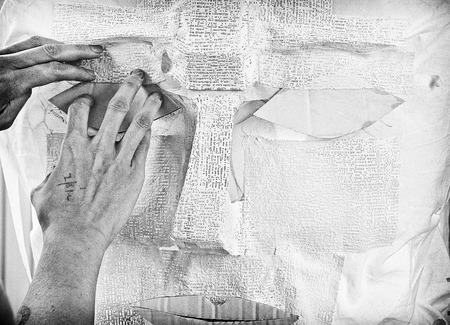 Textured image in black and white of artists hands working with plaster.
